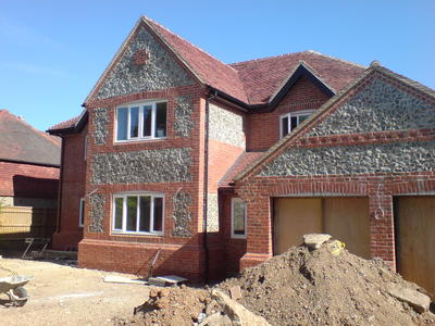 New build house finished in brick and flint to complement the surrounding area